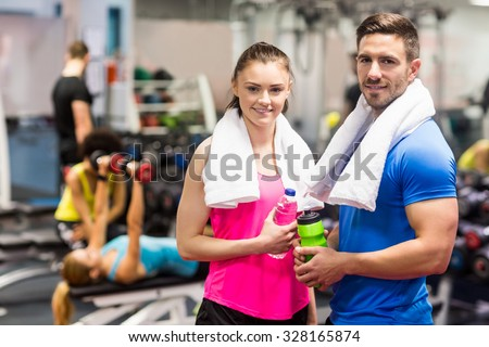 Fit couple smiling at camera at the gym - stock photo