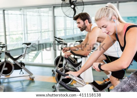 Fit couple using exercise bikes at the gym - stock photo