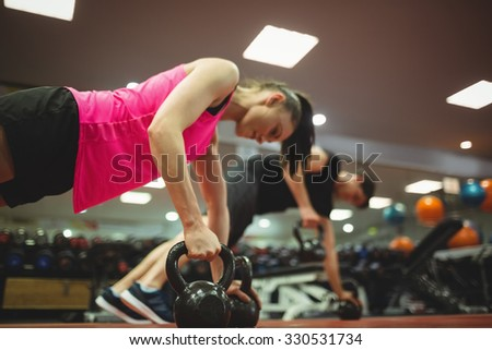 Fit couple working out in weights room at the gym - stock photo