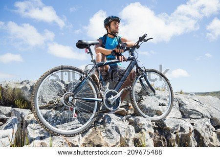 Fit cyclist taking a break on rocky peak on a sunny day - stock photo