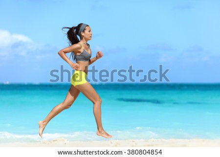 Fit female athlete girl runner running on beach. Full length body of woman jogging fast barefoot on sand training doing her cardio workout during summer vacation living a healthy lifestyle. - stock photo