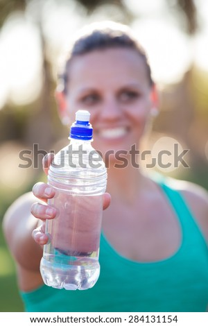 Fit female athlete holding out her water bottle towards the viewer just before she starts to train on a tartan athletics track - stock photo