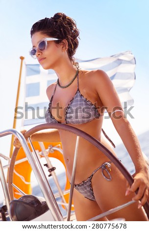 Fit female behind wheel of sailboat, fashion model on posing on water transport, woman traveling along sea, summer vacation concept  - stock photo