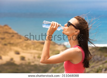 Fit female drinking a bottle of water. - stock photo
