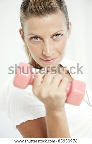 fit female holding a dumbell, looking at camera - stock photo