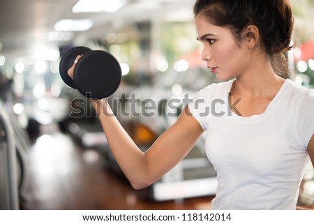 Fit female lifting dumbbell to build biceps - stock photo