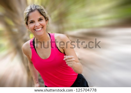Fit female runner working out and looking very happy - stock photo