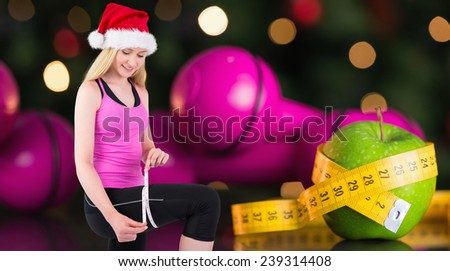 Fit festive young blonde measuring her thigh against measuring tape - stock photo