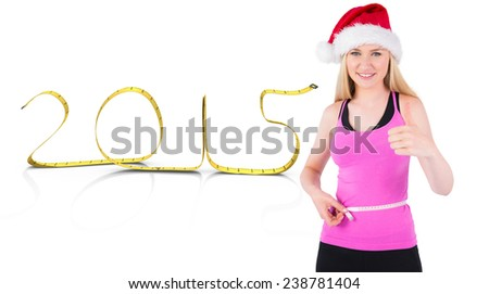 Fit festive young blonde measuring her waist against measuring tape 2015 - stock photo