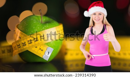 Fit festive young blonde measuring her waist against measuring tape - stock photo