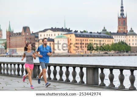 Fit fitness exercise people, healthy runners running in Stockholm city cityscape skyline. Riddarholmskyrkan church in the background, Sweden, Europe. Healthy multiracial young adults. - stock photo