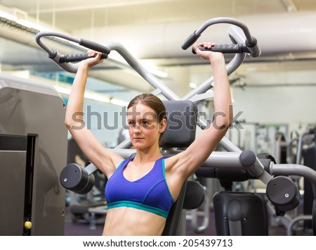 Fit focused brunette using weights machine for arms at the gym
