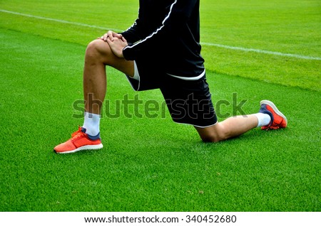 fit football player getting stretching her legs before running   - stock photo