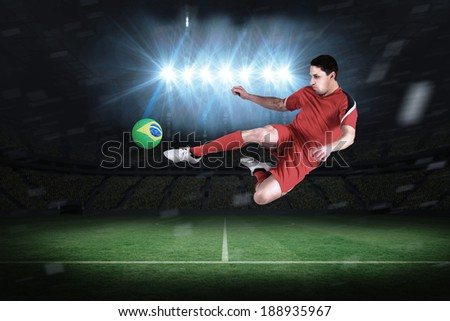 Fit football player jumping and kicking in a football pitch under spotlights