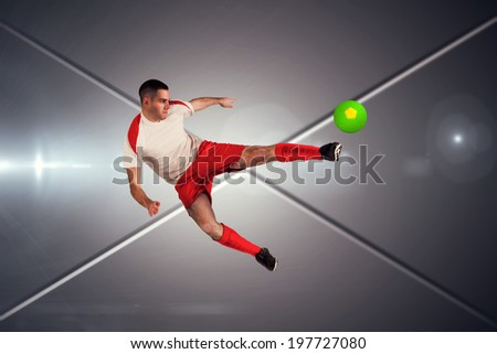 Fit football player playing and kicking against futuristic screen with lines