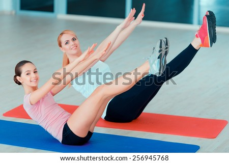 Fit for life. Top view of beautiful teenage girl and her mother in sports clothing training yoga and taking similar positions on the mat in sports club - stock photo