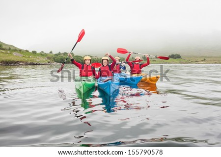 Fit friends rowing on a lake in kayaks and cheering at camera - stock photo