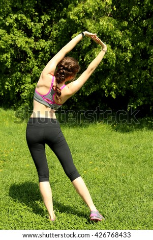Fit girl doing stretching exercise in park, standing back to camera.