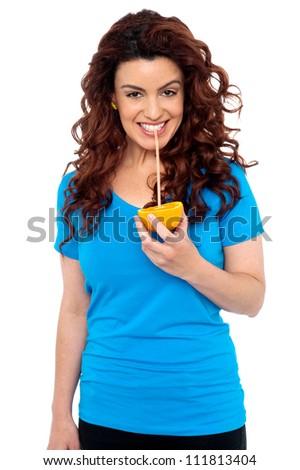 Fit girl drinking fresh orange juice directly from fruit with help of straw - stock photo