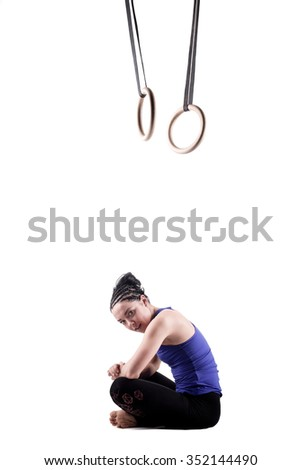 fit girl girl exercising on gymnast rings, against white background - stock photo