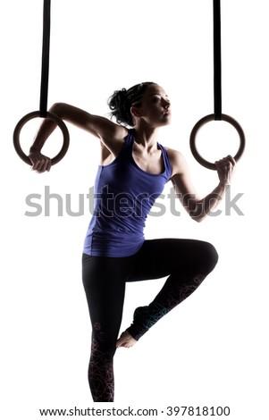 fit girl girl exercising on gymnast rings, against white background - stock photo