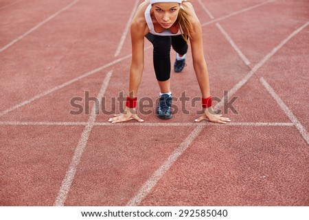 Fit girl in activewear standing at start line - stock photo