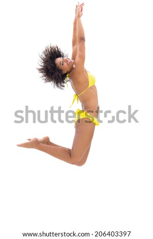 Fit girl in yellow bikini jumping and smiling at camera on white background