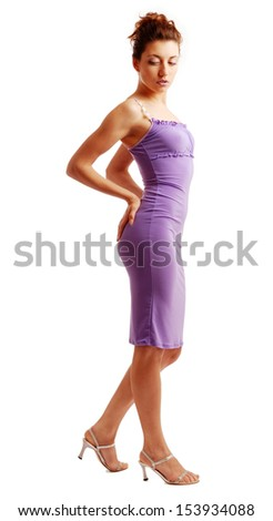 Fit girl is standing and setting a knitted dress straight. The lilac tight-fitting dress is accentuated slender body.