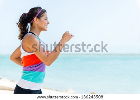 Fit girl running outdoors by the beach