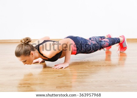 Fit girl with dark hair wearing pink snickers, dark leggings and black short top doing pushups at gym, fitness, white wall and wooden floor, copy space. - stock photo