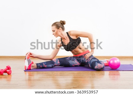 Fit girl with dark hair wearing snickers, dark leggings and black short top doing stretching at gym, fitness, dumbbells, mat and ball on the floor.