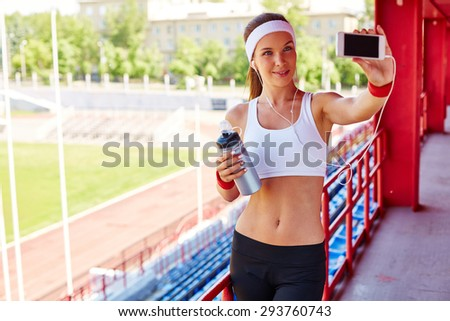 Fit girl with earphones and container making selfie at stadium