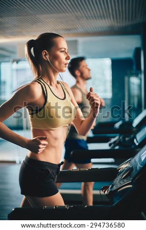 Fit girl with earphones running on treadmill in sports club - stock photo