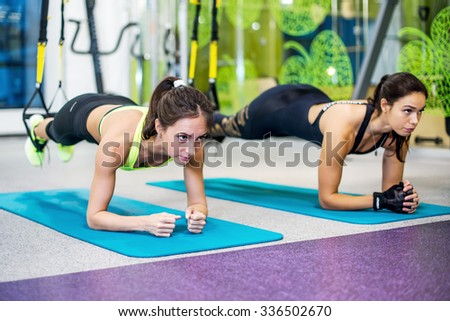 Fit girls in gym doing plank exercise for back spine and posture Concept pilates fitness sport - stock photo