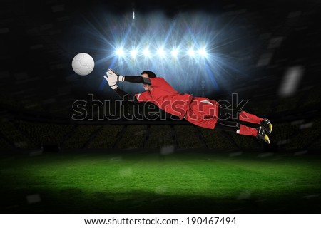Fit goal keeper jumping up against football pitch under spotlights - stock photo