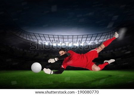 Fit goal keeper jumping up against large football stadium with fans in yellow - stock photo