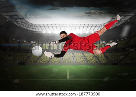 Fit goal keeper jumping up in a large football stadium with lights - stock photo