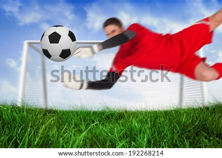 Fit goal keeper jumping up saving ball against field of grass under blue sky - stock photo