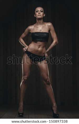 Fit gorgeous brunette in full length on wooden background - stock photo