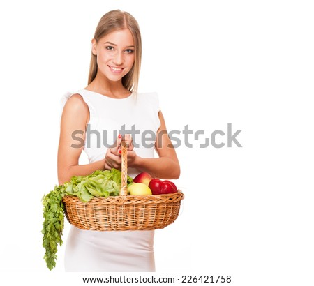 Fit gorgeous young blond woman holding wicker basket full of fresh vegetables.