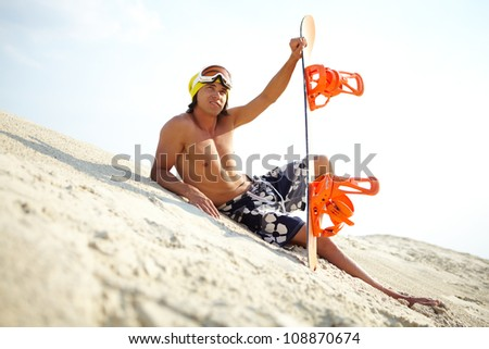 Fit guy relaxing on the beach holding snowboard - stock photo