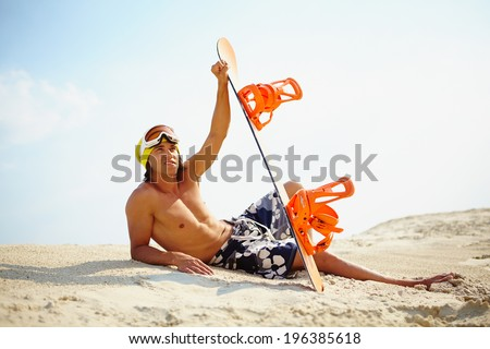 Fit guy with snowboard relaxing on the beach - stock photo