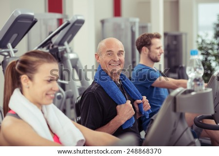 Fit happy senior man in a gym working out with two younger people on equipment pausing to give the camera a beaming smile full of vitality - stock photo