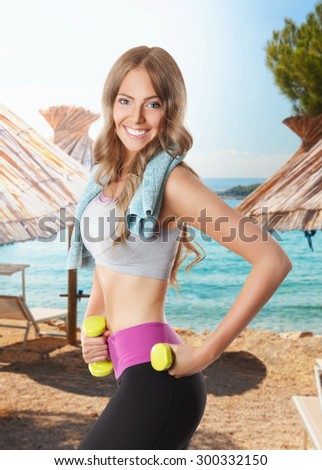 Fit happy woman doing a workout on the beach - stock photo