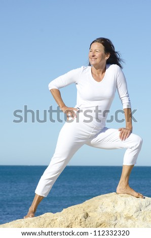 Fit, healthy, confident looking attractive senior woman exercising, stretching on top of rock, isolated with ocean and blue sky as background and copy space. - stock photo