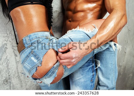 Fit healthy couple sexualy hugs one another standing - stock photo