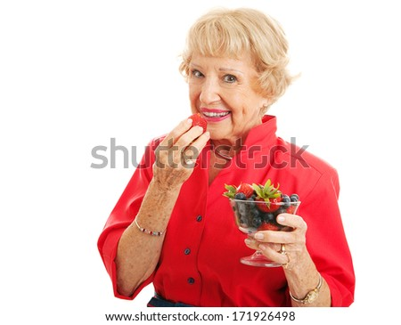 Fit healthy senior woman biting into a strawberry and holding a bowl of mixed berries.