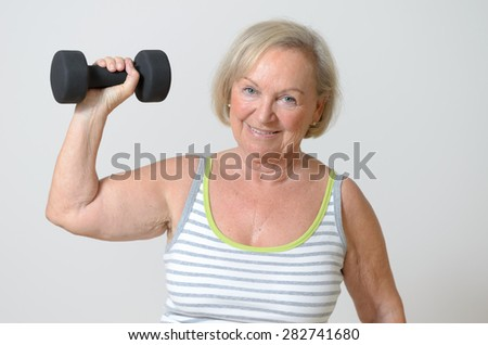 Fit healthy strong senior lady holding a dumbbell in her hands in a conceptual image of health, fitness and diet for a healthy lifestyle
