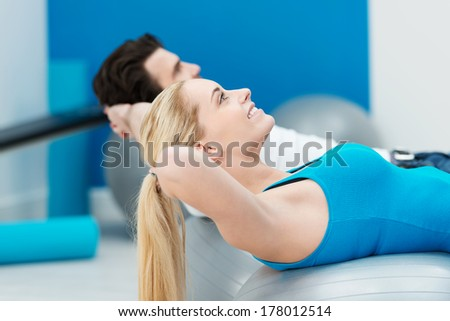 Fit healthy young couple working out in a gym using Pilates gym balls stretching and flexing their muscles to tone their bodies with focus to a beautiful blond woman - stock photo