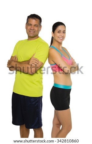 Fit Hispanic couple in workout attire standing back to back - stock photo